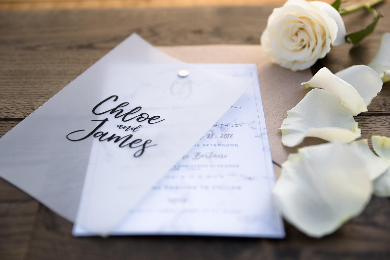 Mugga Design partecipazione effetto marmo marble in carta Modigliani logo monogrammed nomi sposi in carta vegetale, busta kraft e rose sullo sfondo di legno